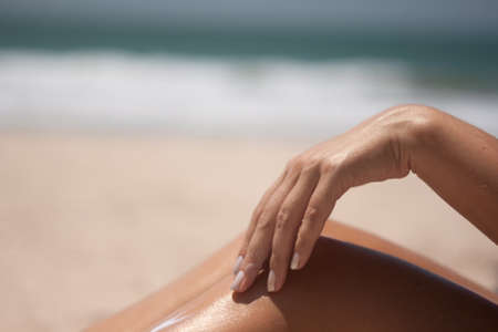 Woman does hand on his leg sunscreen at the beach photo