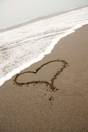 romantic heart drawn in the sand on the beach in Valentines Day photo