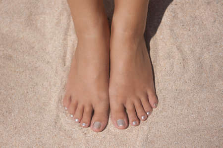 barefoot people: womens feet and hands on the beach beautiful skin