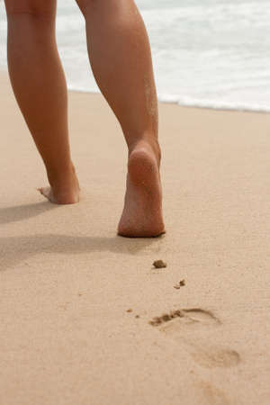 Image of womens legs on the beach and footprints in the sand photo