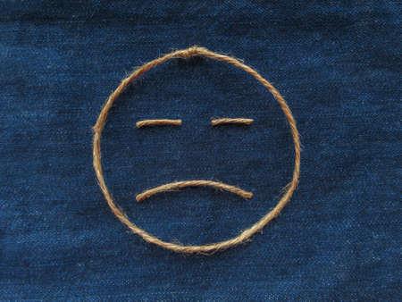Sad face of twine in denim