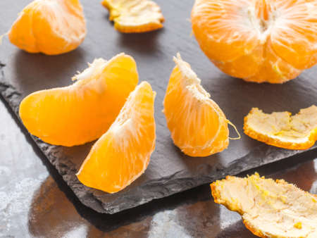 Tangerines slices on black background. Orange mandarin 스톡 콘텐츠