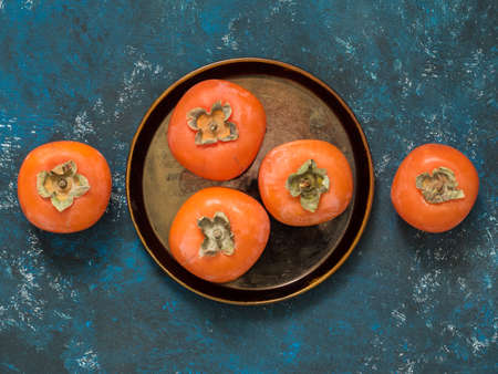 Ripe orange fig persimmon fruit on a blue grunge background. Flat lay. Top view. Copy space Stok Fotoğraf