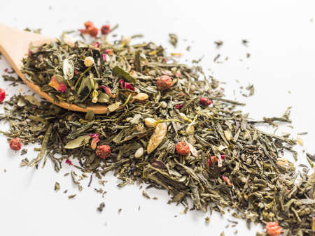 Dry leaves of Sencha green flower tea with cowberry leaf, red currant, Jasmine, rose petals, honey granules, forest berry aroma on white background