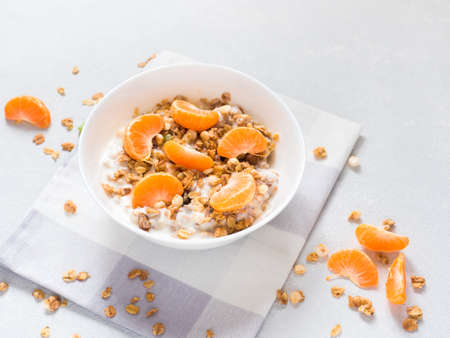 Healthy breakfast. Baked muesli with tropical fruits, fresh tangerines and yogurt on white background