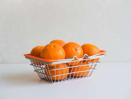 Fresh ripe mandarin oranges fruit or tangerines in small metal food basket on grey background Stock Photo