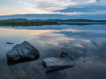 Calm, serenity, meditation concept. Sunset on the lake, stones in the water in the foreground, quiet water, cloudless sky.