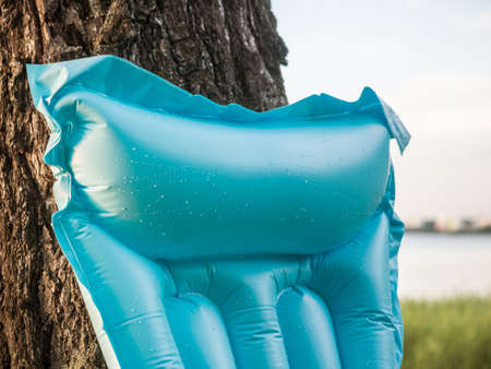 Vacation and recreation concept. Inflatable blue beach mattress for swimming with drops of water leaned against a tree on the background of the beach. Closeup Imagens