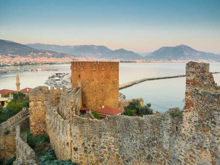 Alanya, Turkey. Beautiful view of the walls of the ancient fortress Alanya castle, the Red Tower K?z?l Kule and The Mediterranean Sea. Vacation postcard background