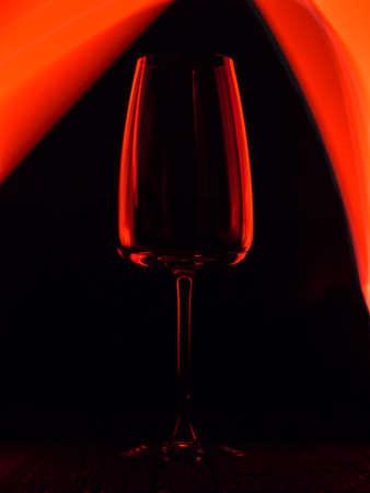 Wine glass on a dark colored background. Glare in the glass, minimalistic beautiful concept. Фото со стока - 135731559