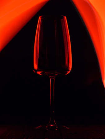 Wine glass on a dark colored background. Glare in the glass, minimalistic beautiful concept.