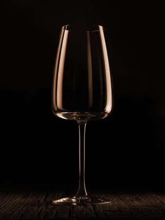Wine glass on a dark colored background. Glare in the glass, minimalistic beautiful concept. Фото со стока