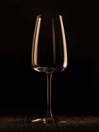 Wine glass on a dark colored background. Glare in the glass, minimalistic beautiful concept. Фото со стока - 136635235