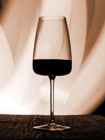 Wine glass on a dark colored background. Glare in the glass, minimalistic concept