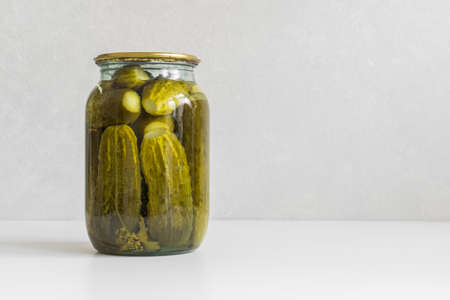 Fermented vegetables. Glass jar with homemade pickled ugly cucumbers on a white background. Copy space, close-up.
