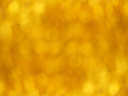 Gold bokeh. Yellow beautiful festive abstract background. Blurry light. Фото со стока