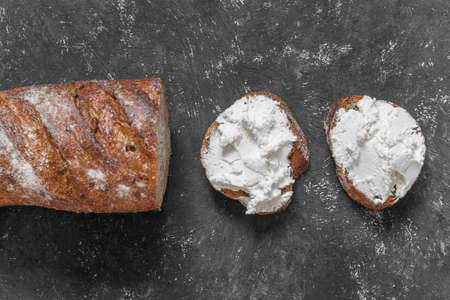 Whole grain bread bruschetta with white soft curd cream cheese on a black background. Top view. Close-up.