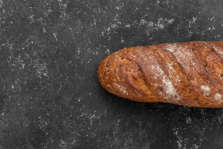 Loaf of whole grain bread on a black background. Baked waste concept. Close-up, top view.
