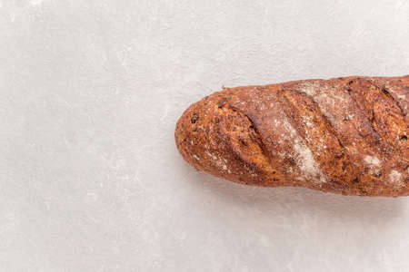 Loaf of whole grain bread on a white background. Baked waste concept. Close-up, top view.