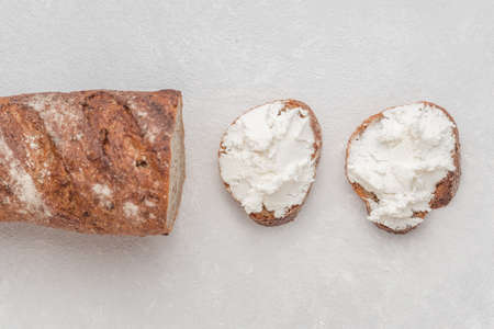 Whole grain bread bruschetta with white soft curd cream cheese on a white background. Top view. Close-up Stok Fotoğraf
