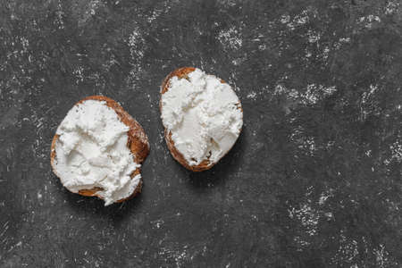 Whole grain bread bruschetta with white soft curd cream cheese on a black background. Top view. Close-up Stok Fotoğraf