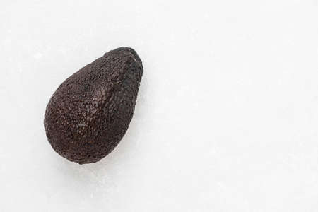 Whole ripe brown hass avocado fruit on white background. Healthy fats. Top view, copy space.