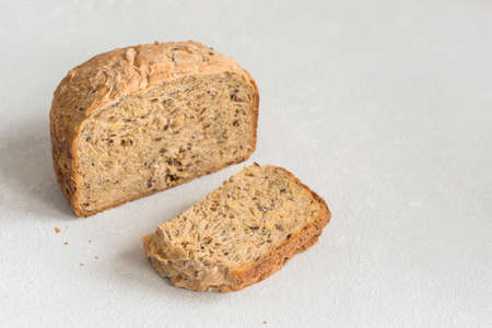 Half a loaf of homemade whole grain bread with various seeds and two slices on a white background. Healthy natural fresh food. Close-up.