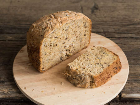 Half a loaf of homemade whole grain bread with various seeds and two slices on a wooden background. Healthy natural fresh food. Close-up.