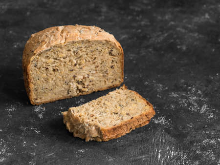 Half a loaf of homemade whole grain bread with various seeds and two slices on a black background. Healthy natural fresh food. Close-up.