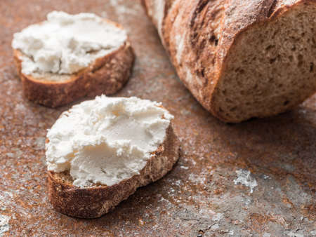 Whole grain bread bruschetta with white soft curd cream cheese on a ginger grunge background. Close-up.