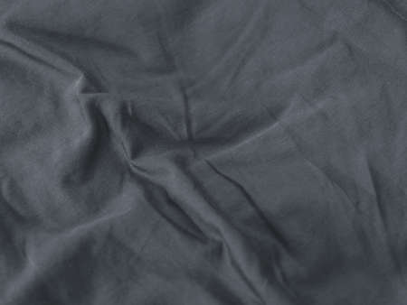Chemical free textile concept. Folds on gray fabric background. Linens
