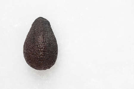 Whole ripe brown hass avocado fruit on white background. Healthy fats. Top view, copy space