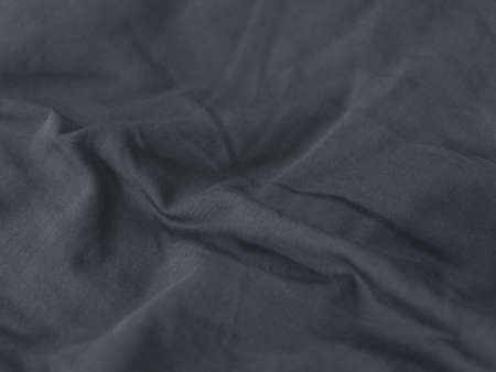 Chemical free textile concept. Folds on gray fabric background. Linens.
