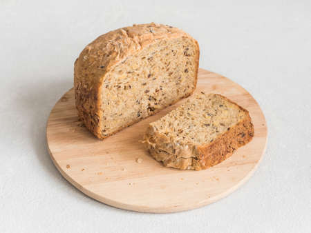 Half a loaf of homemade whole grain bread with various seeds and two slices on a white background Stok Fotoğraf