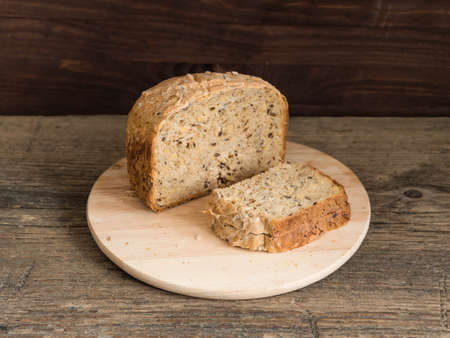 Half a loaf of homemade whole grain bread with various seeds and two slices on a wooden background