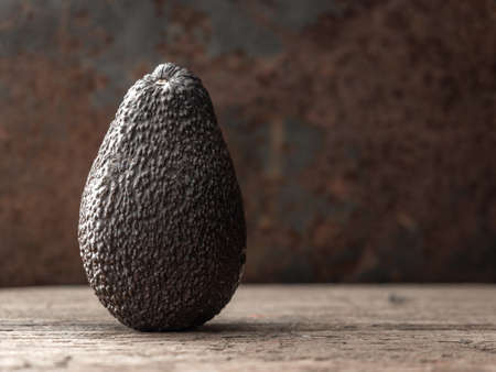 Whole ripe brown hass avocado fruit on dark table. Healthy fats. Side view, copy space. Stok Fotoğraf