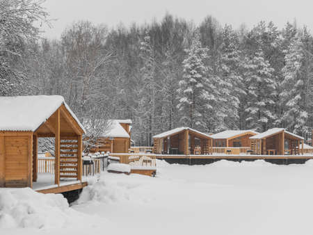 Wooden barbecue houses in a snowy winter park. Pergolas with terraces for outdoor recreation. Stok Fotoğraf