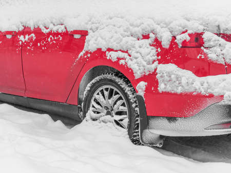 Close-up red car under the snow. Snowfall, bad weather winter concept. Stok Fotoğraf