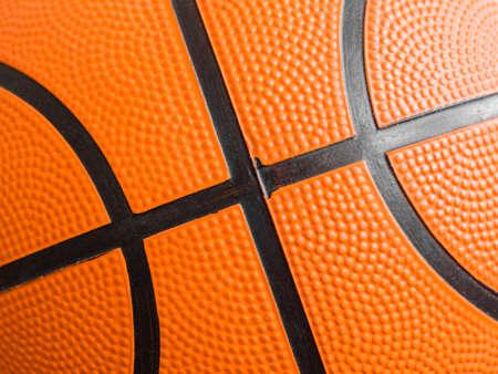 Orange basketball ball close up. Fragment, black stripes, texture. Sport geometric background