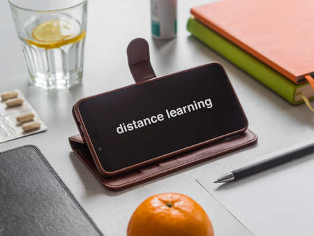 Distance learning or work, online education concept. Workplace. Smartphone, books, glass of water with lemon and pills on the table. Phone screen mockup.