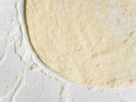 Pizza dough in flour. Ingredient for making homemade pizza on a white table. Close-up