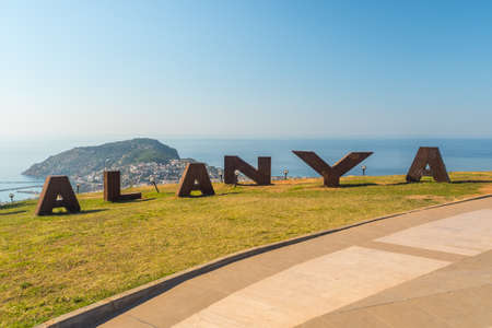 Alanya, Turkey. Big metal letters on the mountain against the background of the Mediterranean Sea. Vacation postcard background 写真素材