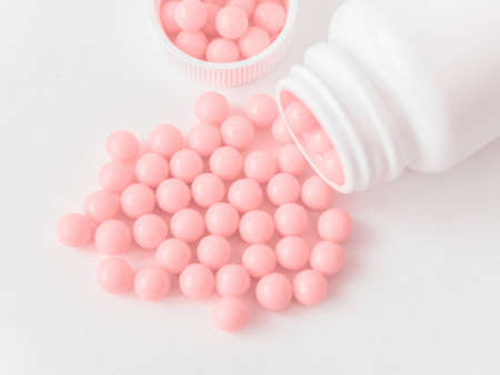 Vitamins. Antiviral drug tablets. Round pink healthy pills and pill bottle on white background. Homeopathic globules, alternative homeopathy medicine. Minimalistic concept.