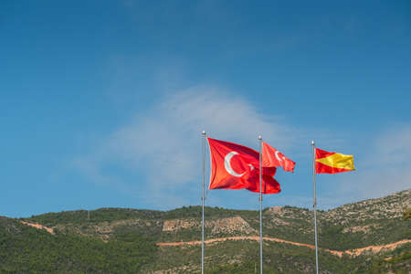 Alanya, Turkey. Red flags of Turkey on background of blue sky and mountains. Vacation postcard background Imagens