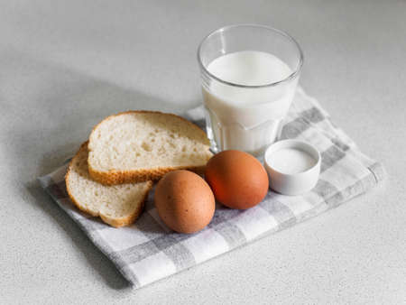 Breakfast ingredients. Still life of eggs, milk and bread on a white background. Close-up 写真素材