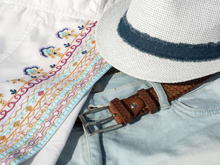 Flat lay fashion women summer beachwear accessories: shorts, shirt, hat, belt. Travel vacation background. Top view