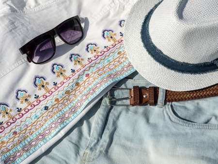 Flat lay fashion women summer beachwear accessories: sunglasses, shirt, hat, belt. Travel vacation background. Top view 写真素材
