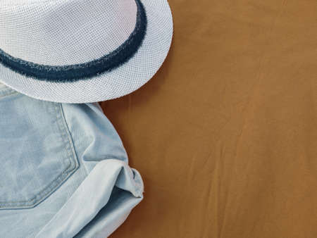 Flat lay fashion women summer beachwear accessories: shorts and hat on a beige travel vacation background. Top view. Copy space