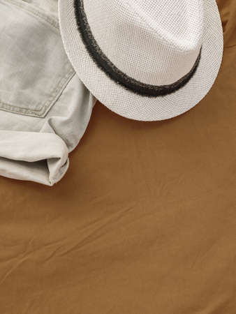 Flat lay fashion women summer beachwear accessories: shorts and hat on a beige travel vacation background. Top view. Copy space.
