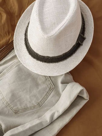 Flat lay fashion women summer beachwear accessories: shorts and hat on a beige travel vacation background. Top view. 写真素材
